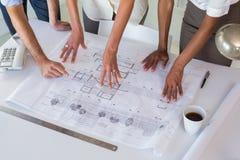 Architectes regardant des plans de bâtiment soigneusement Photo stock