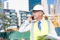 Architector ατόμων υπαίθριο στην περιοχή κατασκευής που έχει την κινητή συνομιλία Στοκ εικόνες με δικαίωμα ελεύθερης χρήσης