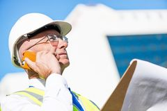Architector ατόμων υπαίθριο στην περιοχή κατασκευής που έχει την κινητή συνομιλία Στοκ φωτογραφία με δικαίωμα ελεύθερης χρήσης