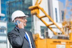 Architector ατόμων υπαίθριο στην περιοχή κατασκευής που έχει την κινητή συνομιλία Στοκ Φωτογραφίες