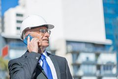 Architector ατόμων υπαίθριο στην περιοχή κατασκευής που έχει την κινητή συνομιλία Στοκ Εικόνα
