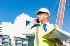 Architector ατόμων υπαίθριο στην περιοχή κατασκευής που έχει την κινητή συνομιλία Στοκ Εικόνες