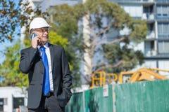 Architector ατόμων υπαίθριο στην περιοχή κατασκευής που έχει την κινητή συνομιλία Στοκ εικόνα με δικαίωμα ελεύθερης χρήσης