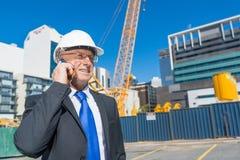 Architector ατόμων υπαίθριο στην περιοχή κατασκευής που έχει την κινητή συνομιλία Στοκ Φωτογραφία