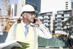Architector ατόμων υπαίθριο στην περιοχή κατασκευής που έχει το κινητό conve Στοκ Φωτογραφίες