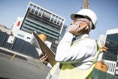 Architector ατόμων υπαίθριο στην περιοχή κατασκευής που έχει το κινητό conve Στοκ Εικόνες