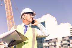 Architector ατόμων υπαίθριο στην περιοχή κατασκευής που έχει το κινητό conve Στοκ Φωτογραφία