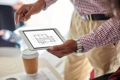 Architector με το σχεδιάγραμμα στο PC ταμπλετών στο γραφείο Στοκ Φωτογραφίες
