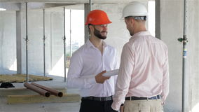 Architector and builder shake hands at the building under construction. Young architector and builder shaking hands at the building under construction. Two stock video footage