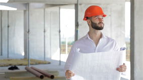 Architector looks at the plan of the building under construction. Male architector looking at the plan of building under construction. Young caucasian stock video