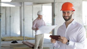 Architector looks at the screen of digital tablet. Male architector looking at the screen of his digital tablet at the building under construction. Close up of stock footage