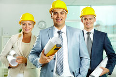 Architects. A smiling architect in helmet with two colleagues near by Stock Photo
