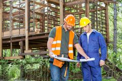 Architects Analyzing Blueprint Outside Incomplete. Male architects analyzing blueprint outside incomplete wooden cabin at construction site stock photography