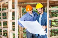 Architects Analyzing Blueprint At Site Stock Photo