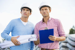 Architects with blueprint and clipboard standing at site Royalty Free Stock Photography