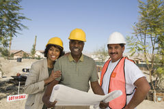 Architects With Blueprint At Construction Site Royalty Free Stock Images