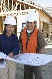 Architects With Blueprint At Site Stock Photo