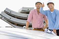 Architects with blueprints on car discussing at construction site Stock Images