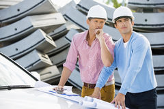 Architects with blueprints on car inspecting site Stock Images