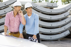 Architects with blueprints on car working at construction site Royalty Free Stock Photo