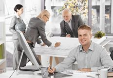 Architects busy at work. Young designer in focus sitting at desk using drawing pad, smiling at camera Stock Photos