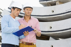 Architects with clipboard working at construction site Royalty Free Stock Image