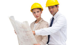 Architects with construction plan and yellow helmets Stock Photography