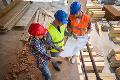 Architects consulting each other about construction plan. Surrounded by materials Royalty Free Stock Photos
