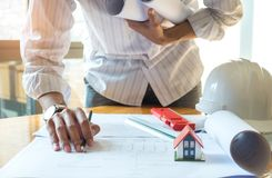 Architects has a pencil in his right hand writing the house,Left hand holding house plan on chest. stock photography