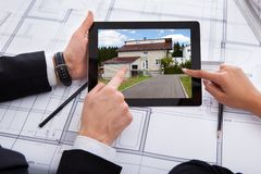 Architects with digital tablet looking at house Royalty Free Stock Photo