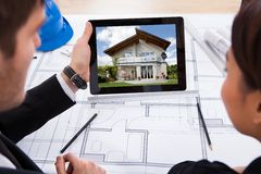 Architects with digital tablet looking at house Stock Photo