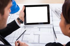Architects with digital tablet working on blueprint Stock Photography
