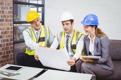 Architects discussing with blueprint Stock Photography