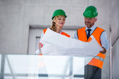 Architects discussing with blueprint in office corridor Royalty Free Stock Photography
