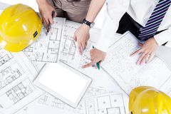 Architects discussing blueprint Stock Images