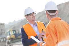 Architects discussing at construction site on sunny day Stock Photos