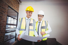 Architects discussing while holding blueprint Stock Photo