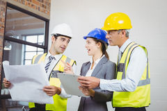 Architects discussing while holding blueprint and clipboard Stock Photography