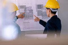 Architects discussing over blueprint on glass board in a modern office. Rear view of Caucasian architects discussing over blueprint on glass board in a modern royalty free stock photography