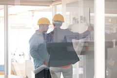Architects discussing over blueprint on glass board. Rear view of Caucasian architects discussing over blueprint on glass board in a modern office stock photo