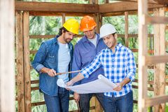 Architects Discussing Over Blueprint At Site Stock Photography
