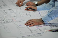 Architects. Discussing Plan Together At Desk Royalty Free Stock Images
