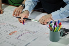 Architects. Discussing Plan Together At Desk Royalty Free Stock Photography