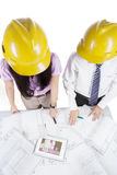 Architects discussing a set of blueprints Royalty Free Stock Photos