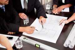 Architects discussing at the table with blueprint Stock Photos