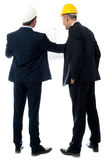 Architects discussing their building plan. Two architects in a suit looking building plan stock photo
