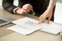 Architects discussing two-story house building plan, property ap. Close up view of two-story house construction project, architects discuss home building Royalty Free Stock Image