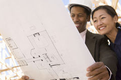 Architects In Discussion Over Blueprint Stock Photos