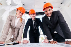 Architects of the drawings. Three businessmеn architect. Met in the office to discuss business projects. Successful young people in the construction helmets royalty free stock images