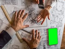 Architects engineer discussing on desk with blueprint. Team group on construciton site check documents and business royalty free stock photo